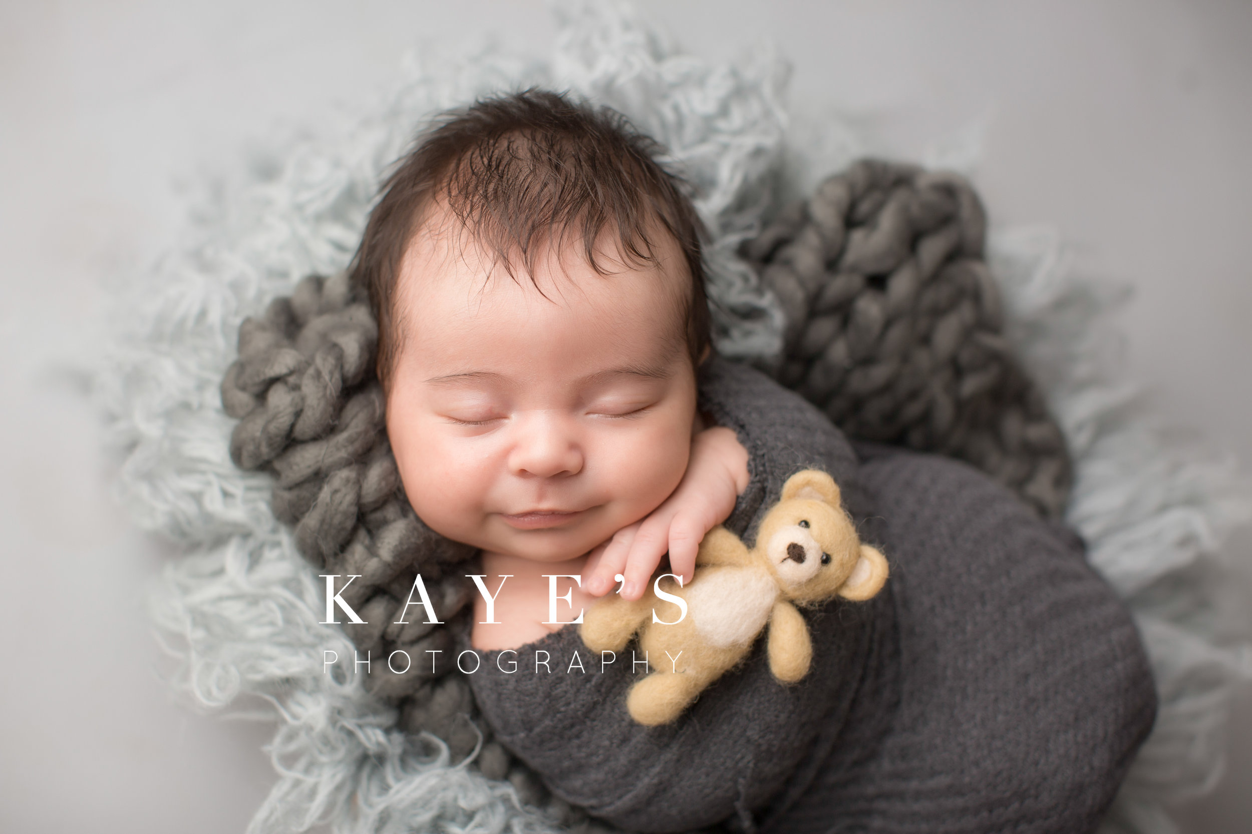 newborn boy holding a bear smiling for baby pictures in photography studio