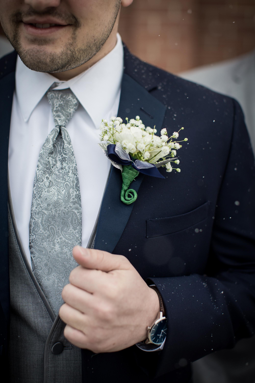 groom posing for wedding photos during winter wedding