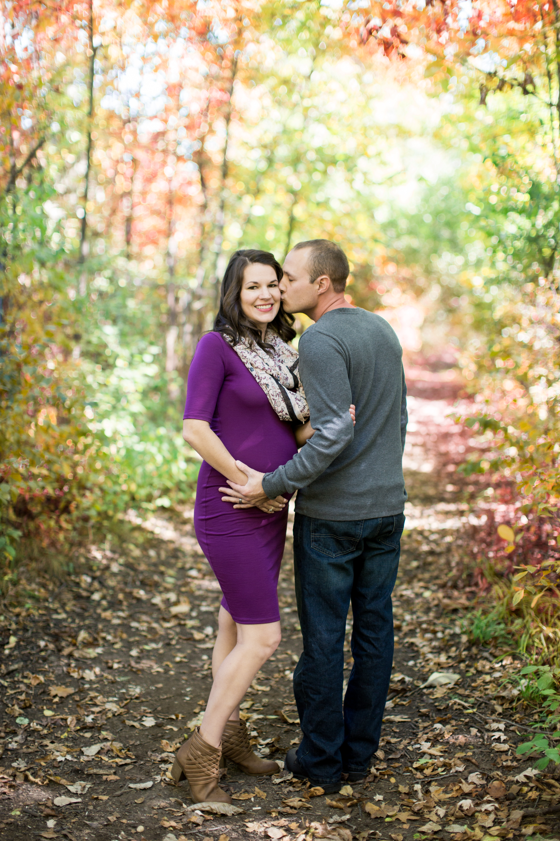 Man kissing pregnant wife on the cheek during a maternity photo session
