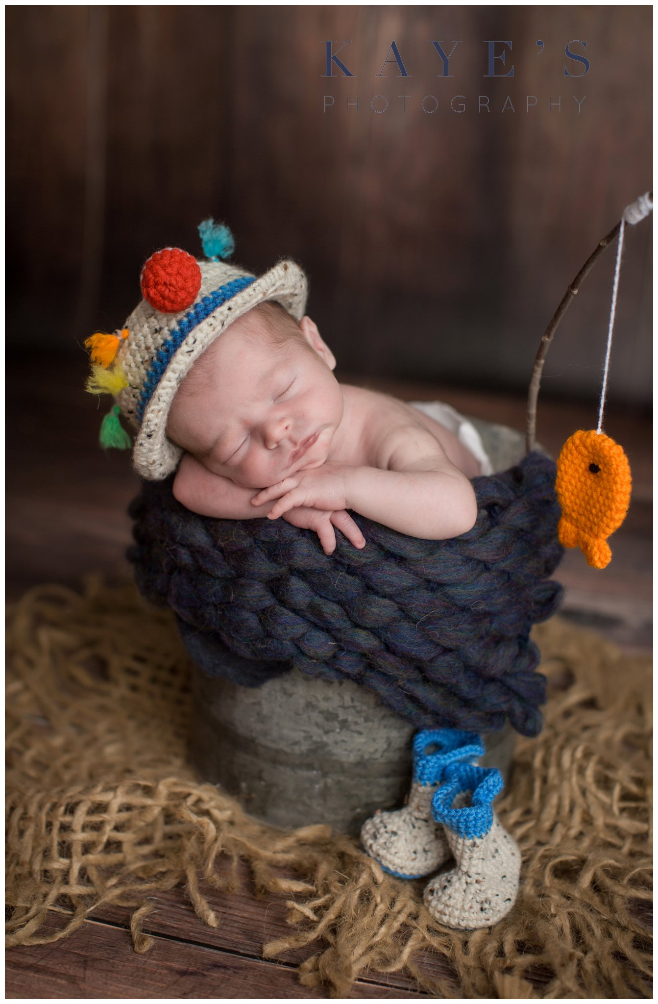 Baby boy in a bucket posing with fishing hat and pole during baby photos