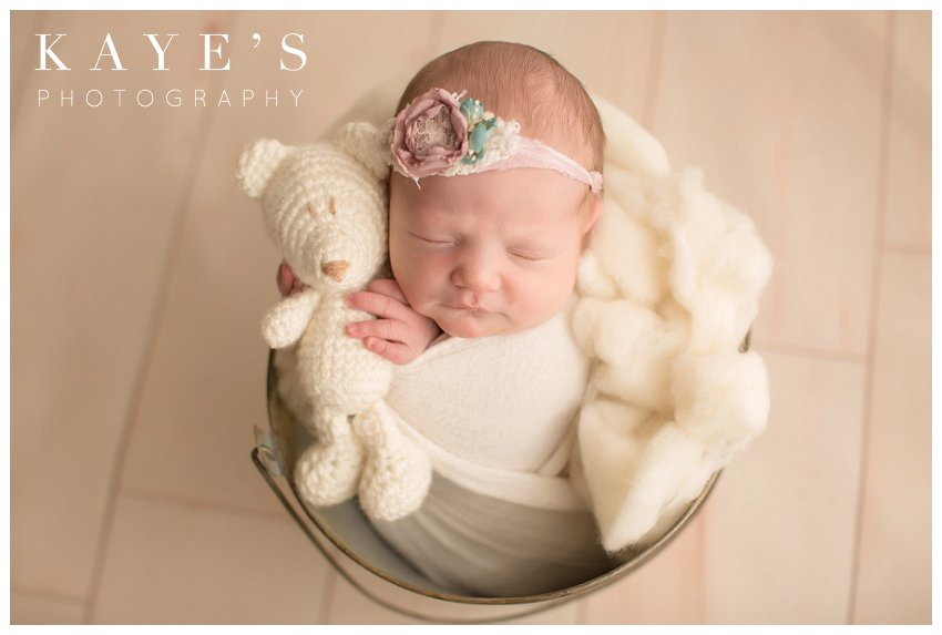 baby girl posing with white bear during professional baby pictures