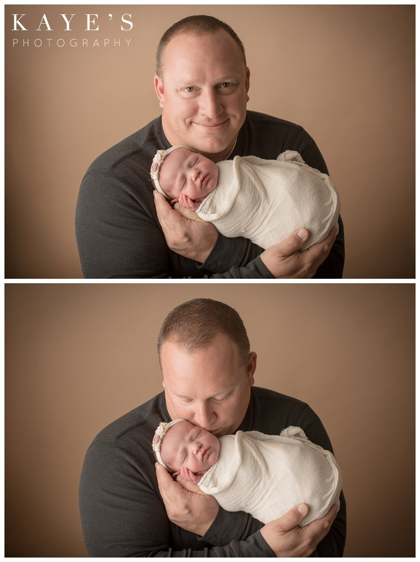Newborn girl with dad during professional baby photos