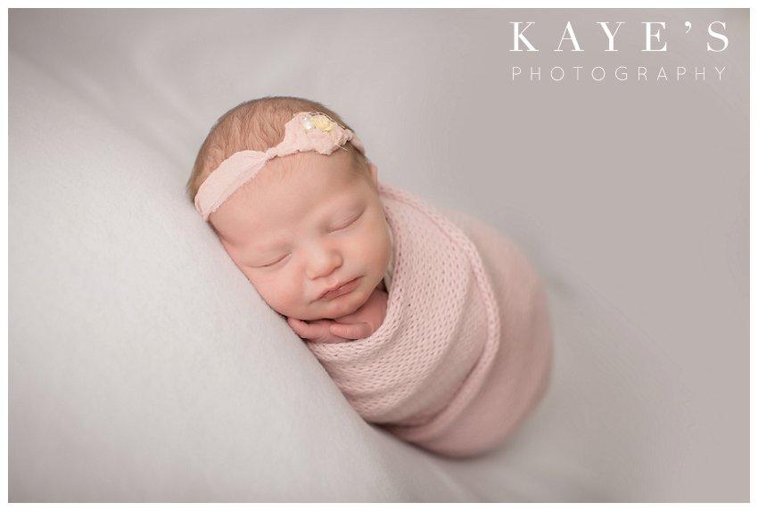Newborn girl posing on white blanket during professional baby photos