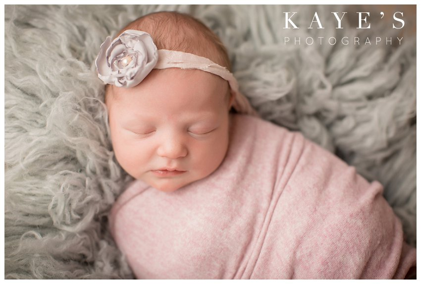 newborn girl on gray rug during profession baby pictures