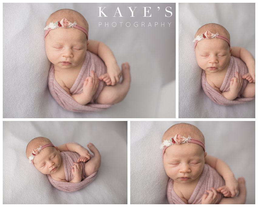 Newborn girl wrapped in pink posing for professional baby pictures