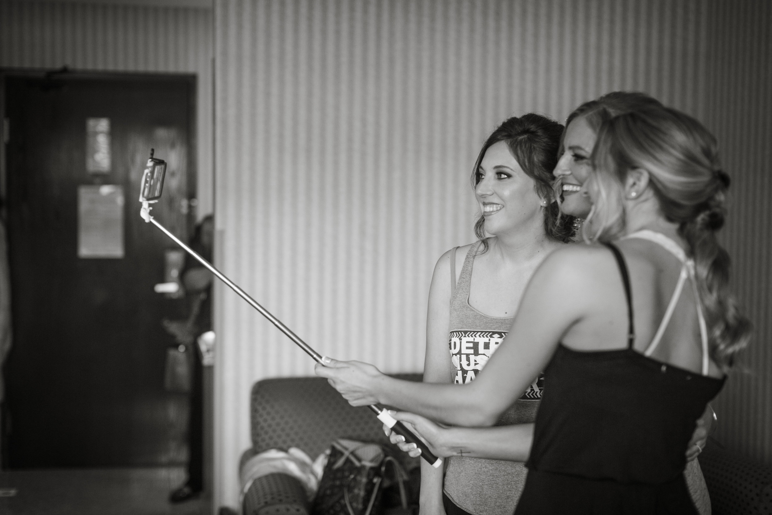 bridesmaid with bride taking photos with selfie stick