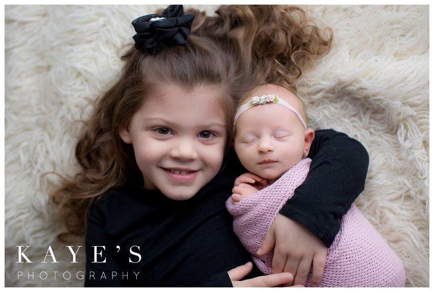 sisterly love during newborn photos in grand blanc michigan
