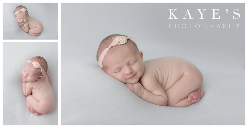 Baby girl on white blanket posed for newborn pictures in grand Michigan