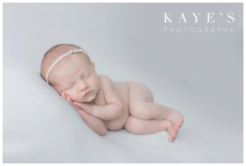 baby girl on white blanket posed during newborn photos in grand blanc Michigan