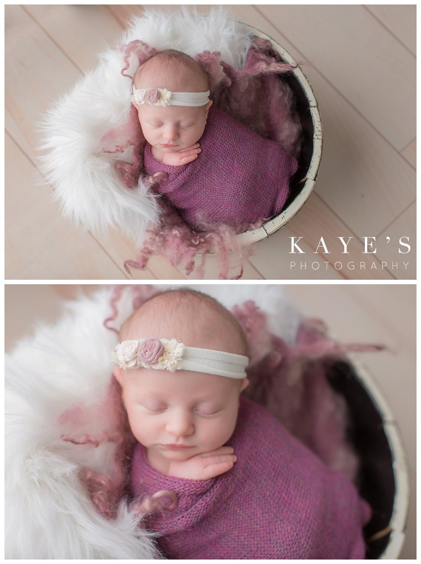 Baby girl wrapped in pink posed in a bucket for newborn baby photos