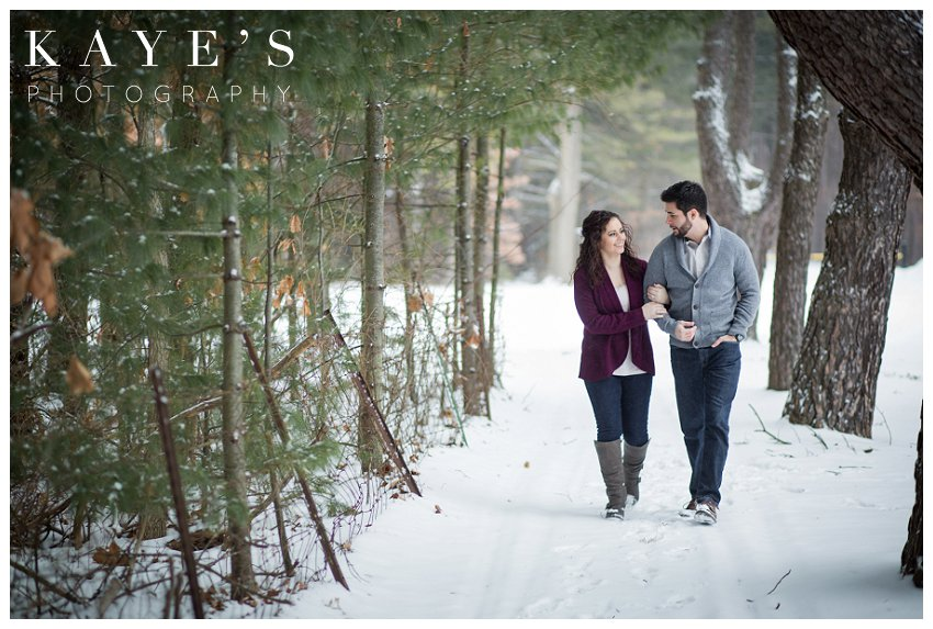 Walking through woods in the snow during winter engagement photos in grand blanc Michigan