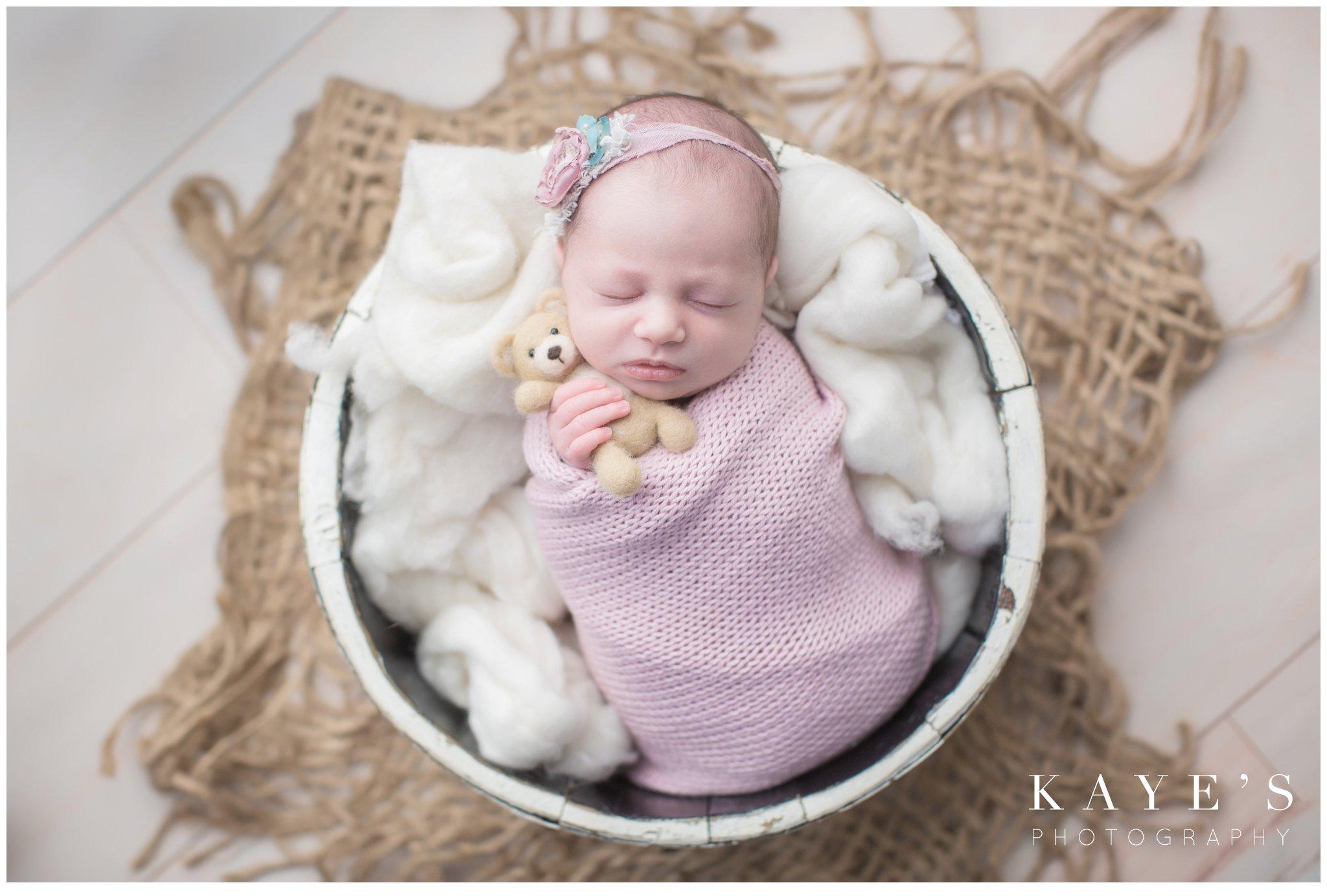 newborn girl in bucket wrapped in pink posing for baby pictures