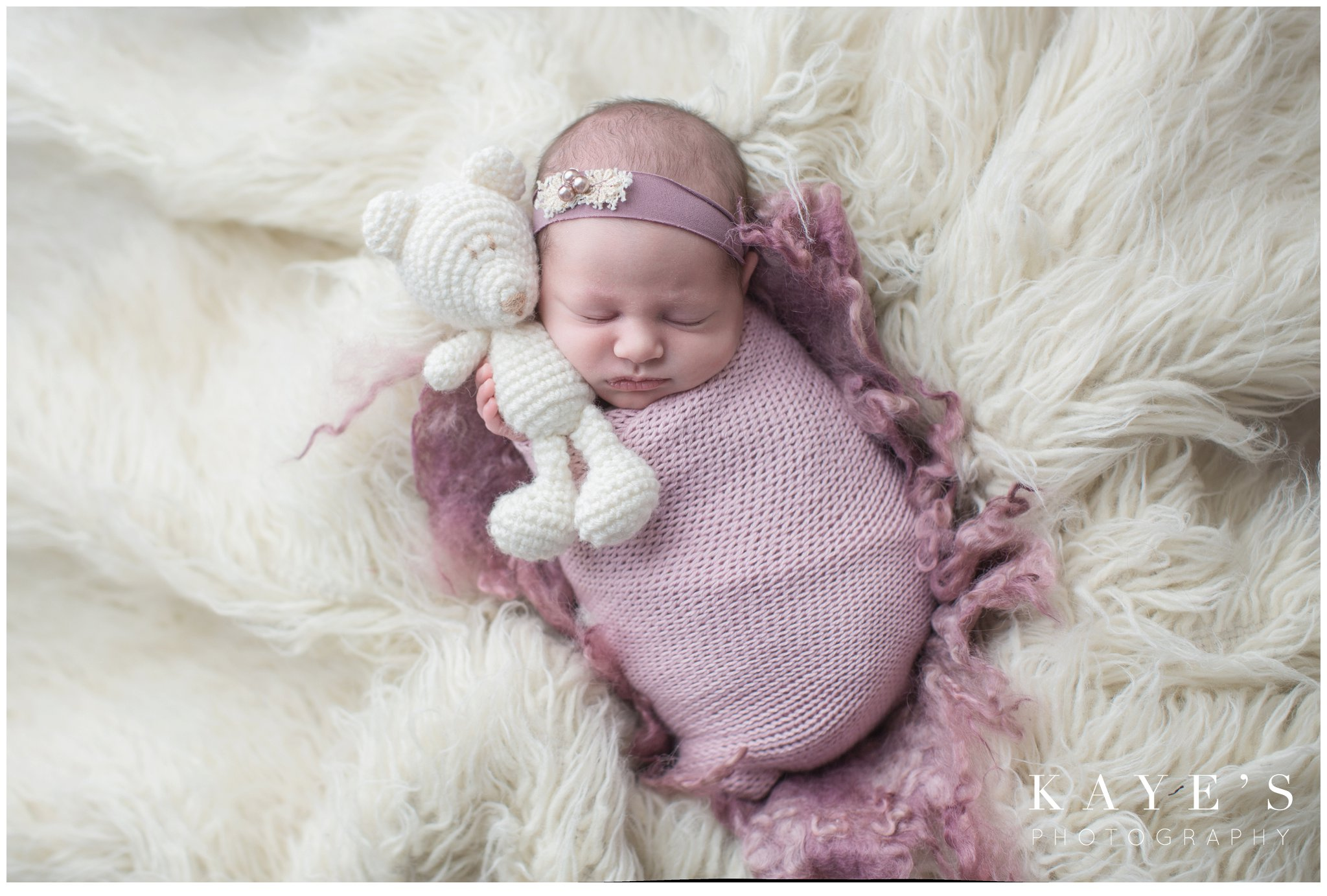 newborn girl holding bear on white rug for baby pictures