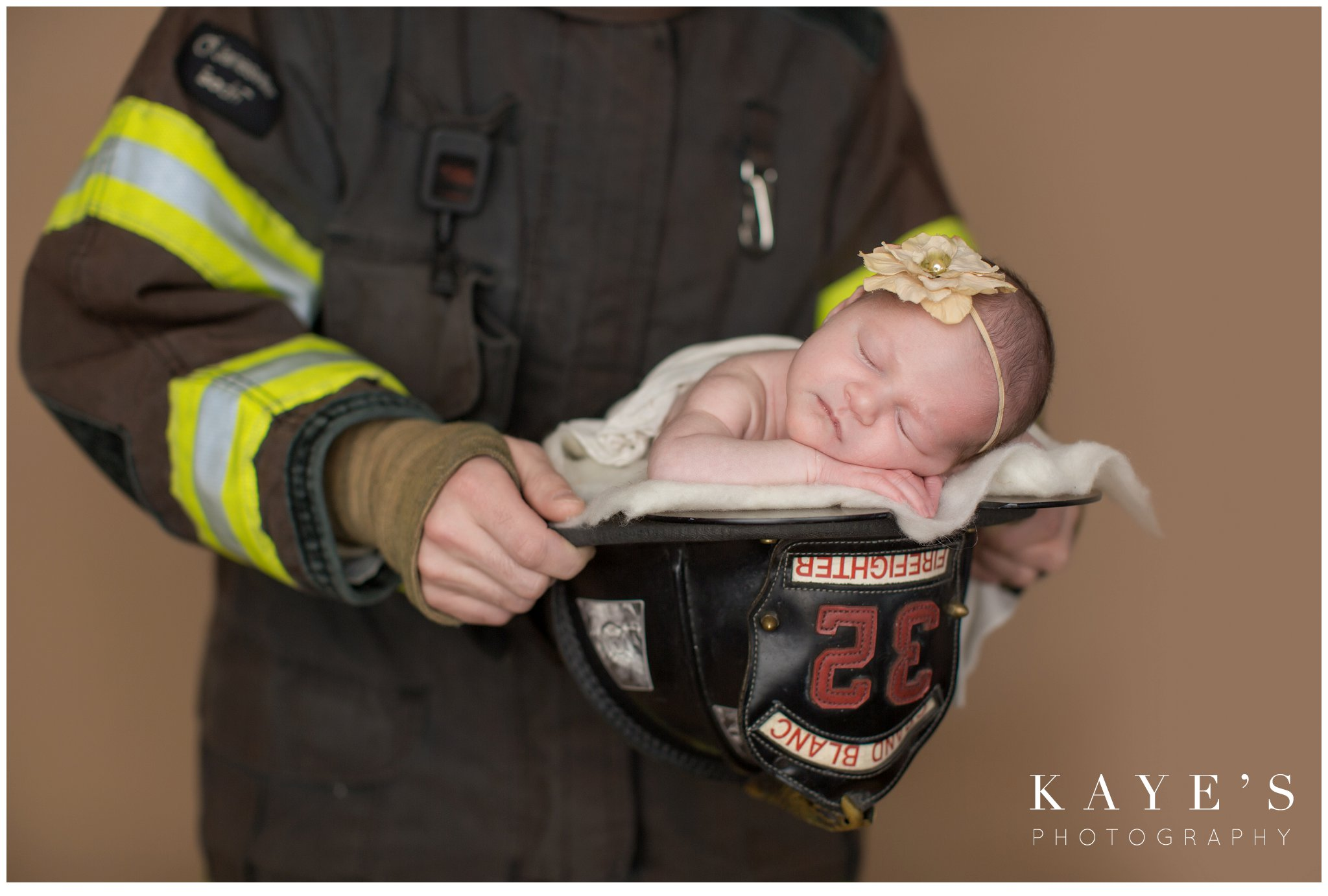 Daddy dressed in fireman gear with newborn baby girl in fireman hat