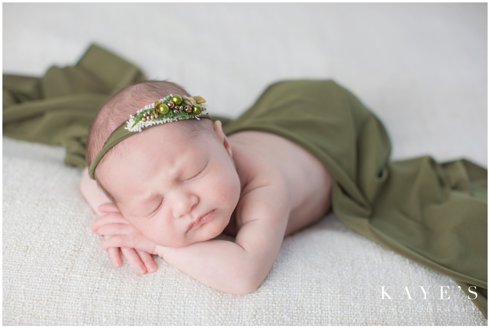 Newborn girl during baby photos wrapped in green on white blanket