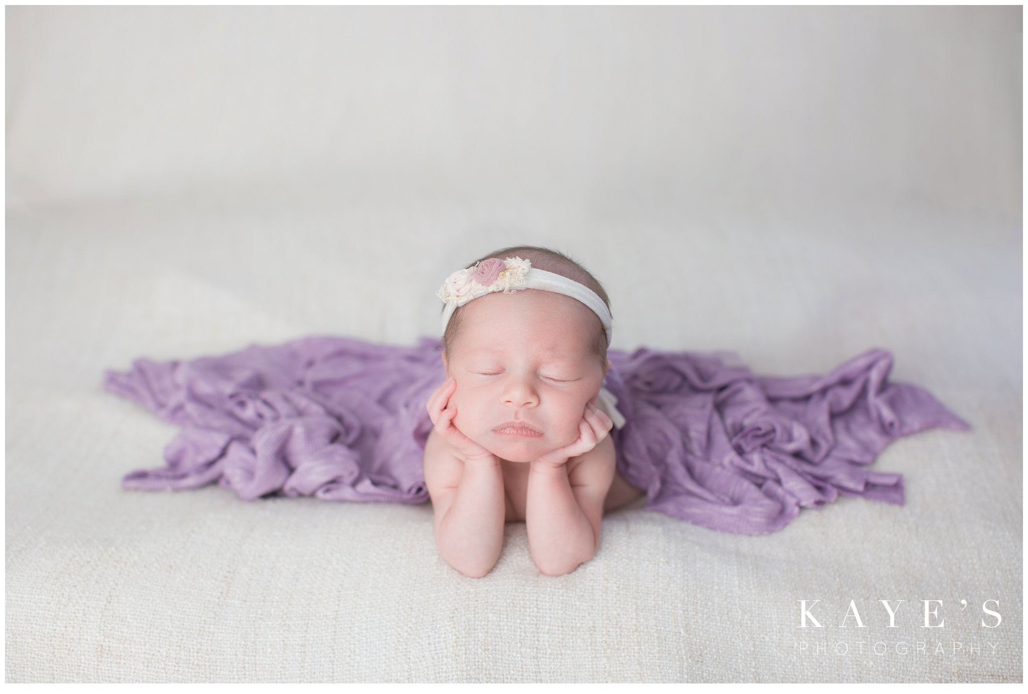 Newborn girl with hands on chin wrapped in purple for baby photos