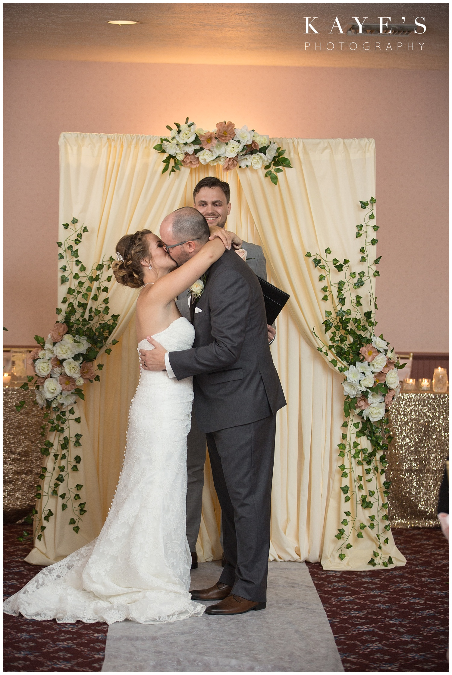 Bride and groom kissing during ceremony at crossroads village in flint!!