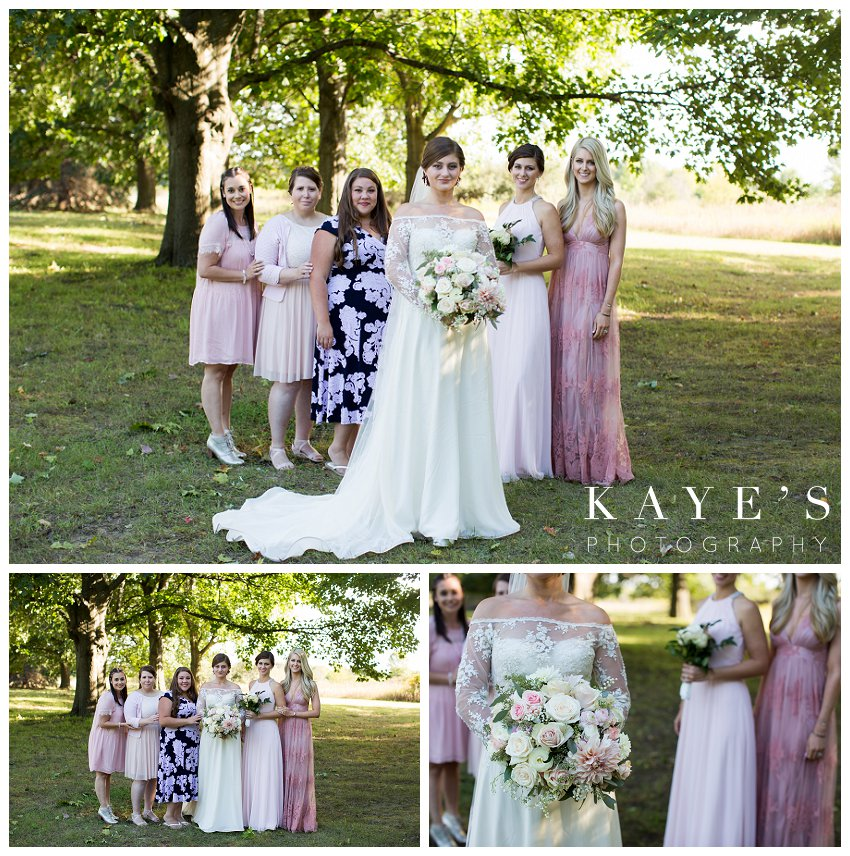 Bride posing with bridesmaids for professional wedding photographer during fall wedding in Flint Michigan