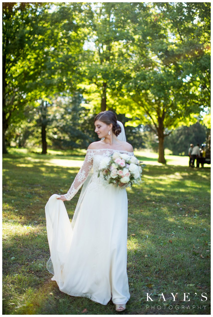 Bride posing for professional wedding photographer during fall wedding in Flint Michigan