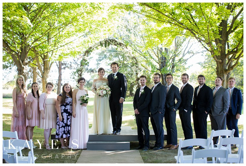 Bride and groom posing with wedding party for professional photographer during fall wedding in Burton michigan