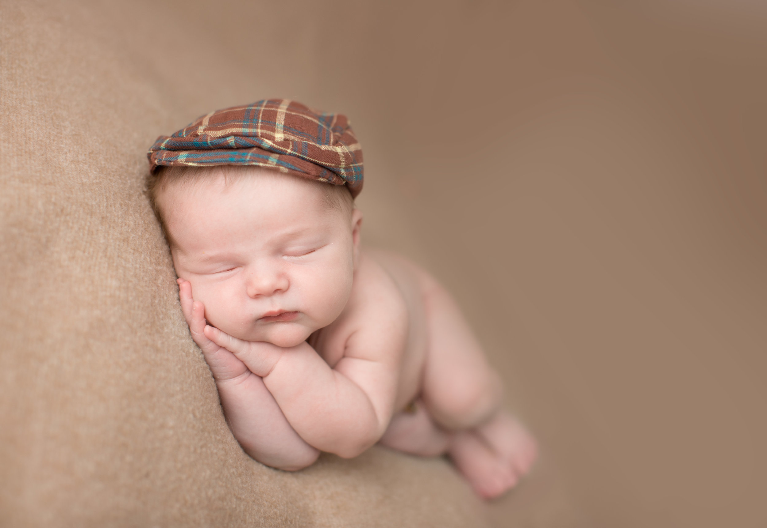 baby boy laying on his side during baby photography session in grand blanc michigan