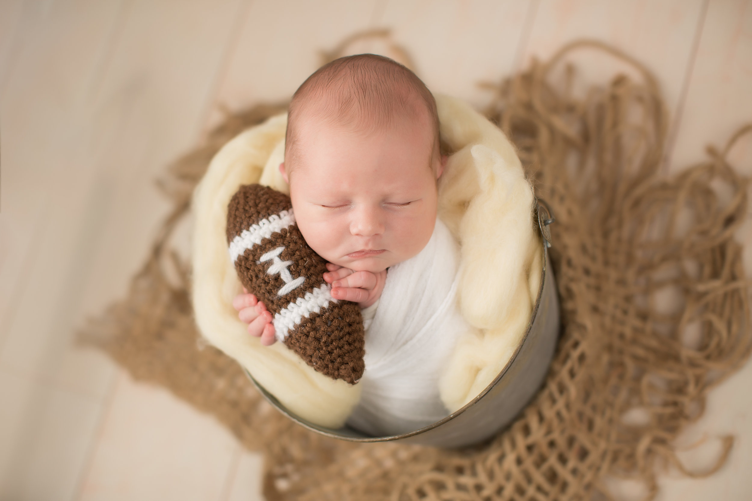 baby boy in bucket holding football for newborn portraits