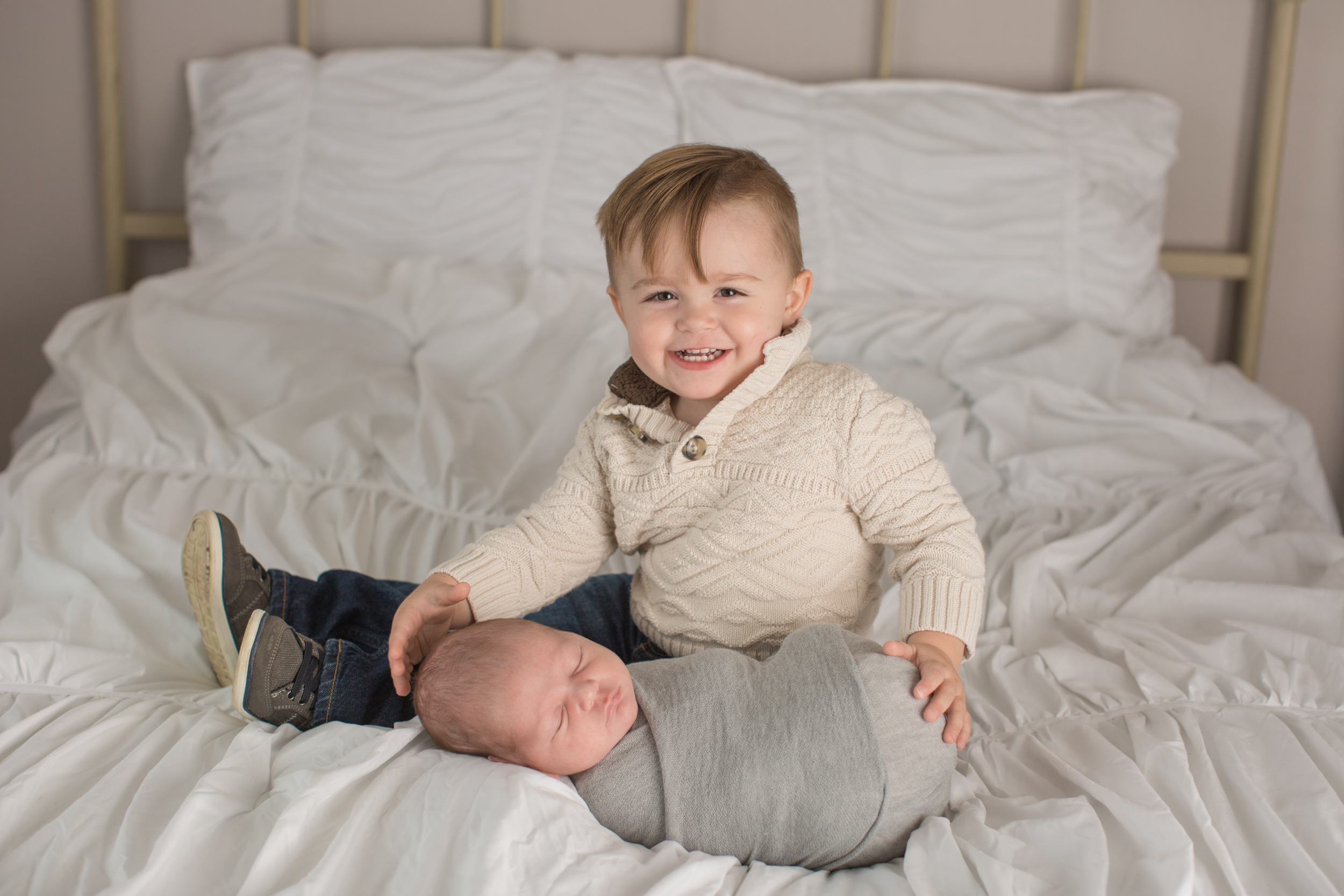 big brother with baby brother during sibling pictures in grand blanc studio with kaye's photography