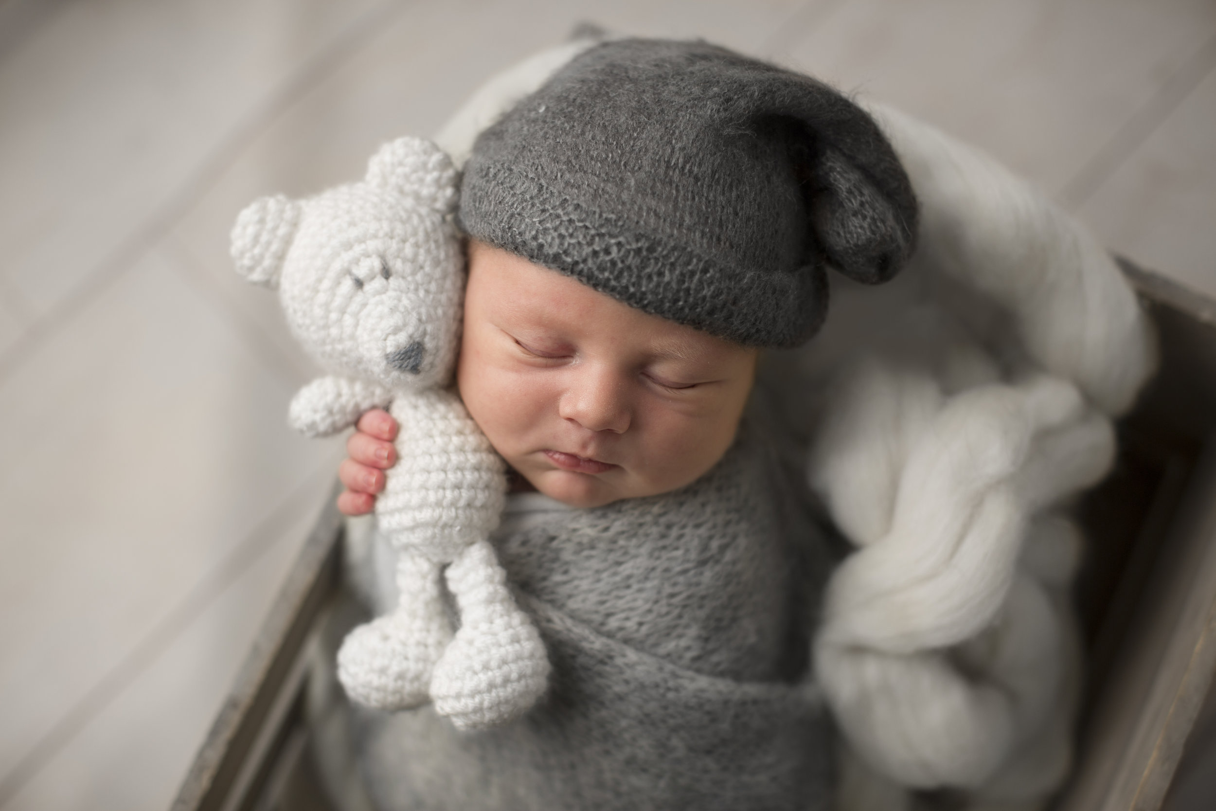 baby boy holding bear in grey during newborn session in genesee county