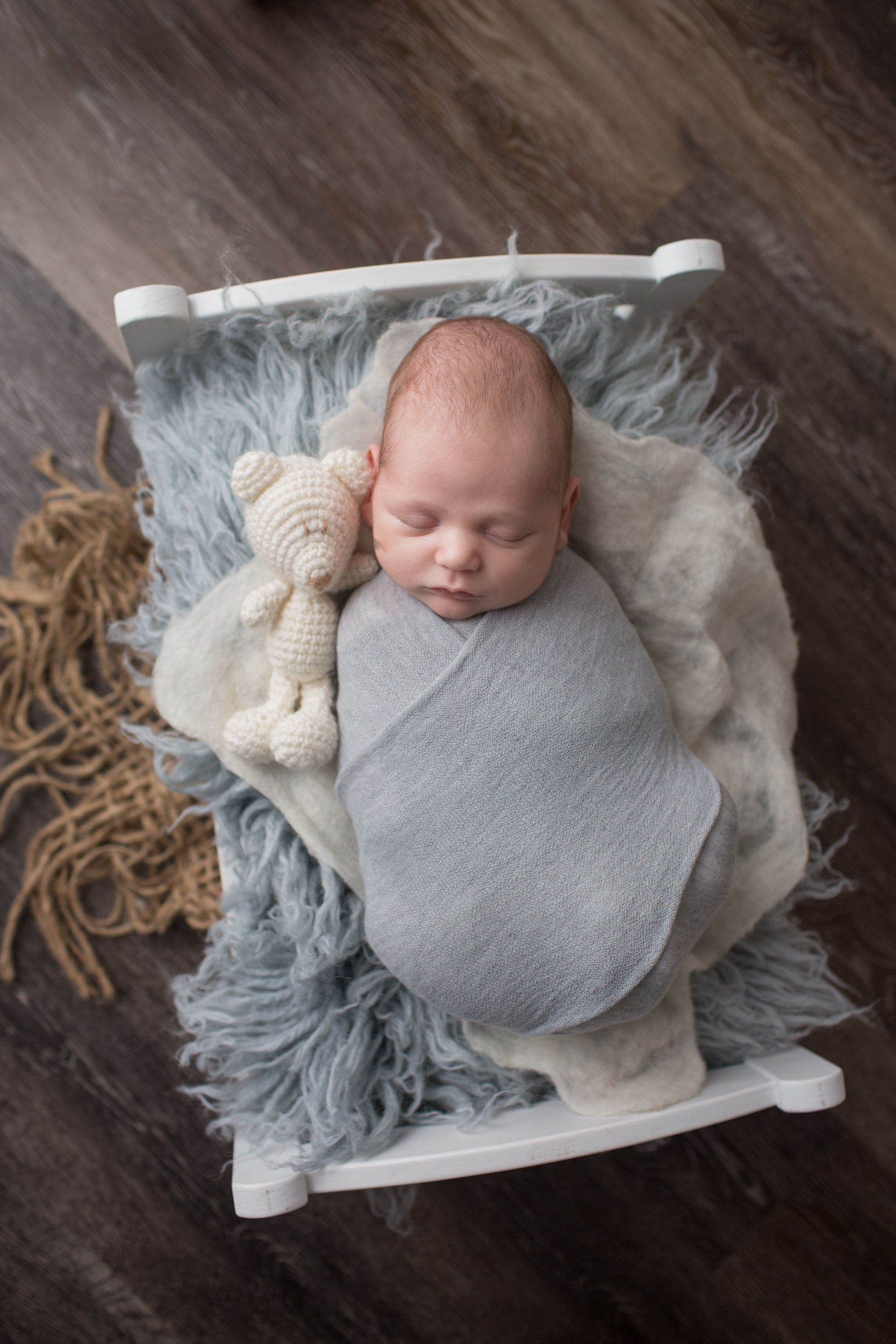 baby boy in bed with bear during baby portrait session with Kaye's Photography