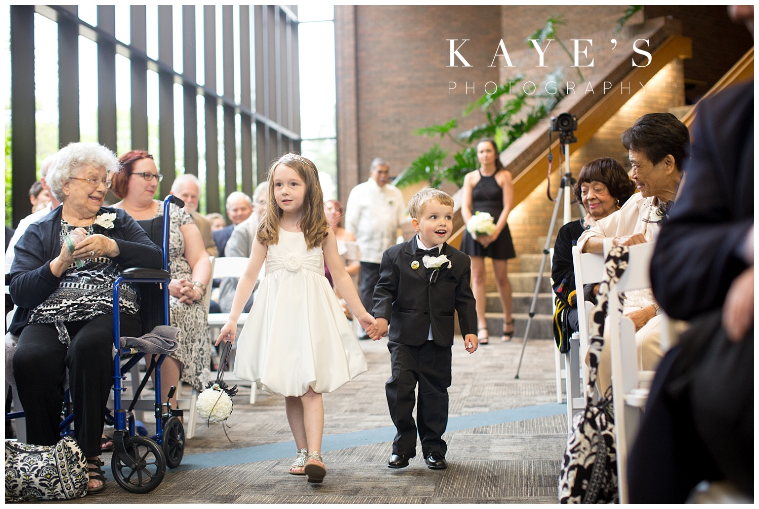 ring bearer and flower girl going down the aisle during the wedding ceremony at university of michigan wedding