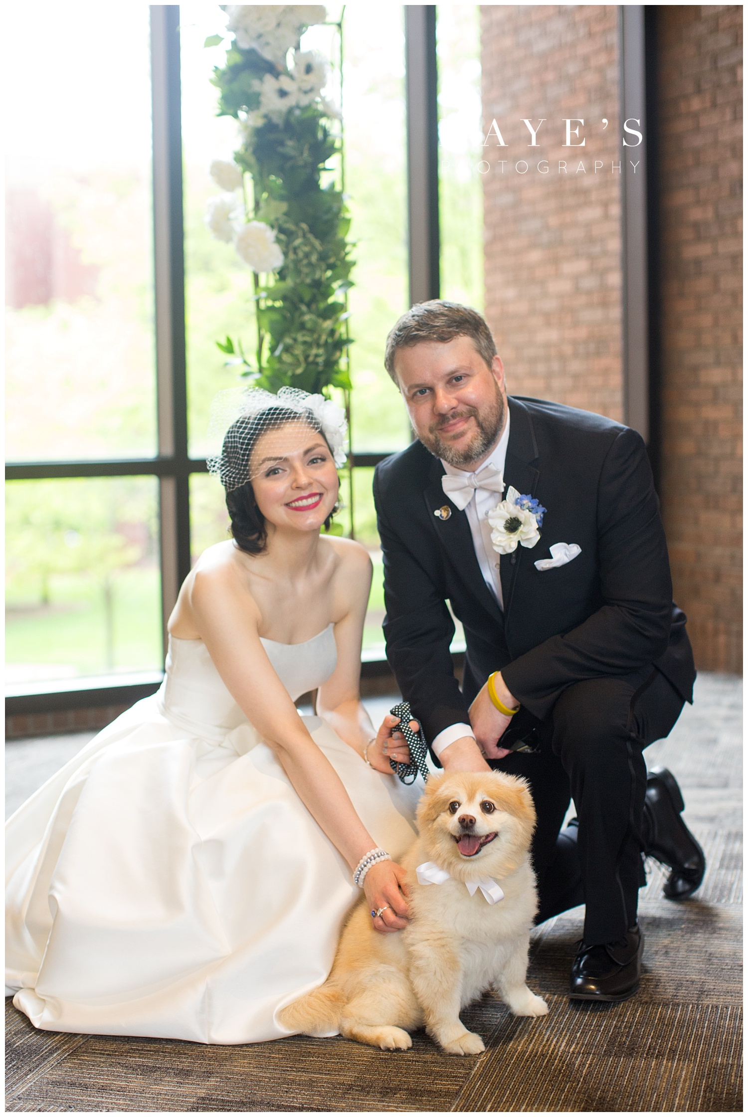 bride and groom with dog during wedding photos after the wedding ceremony