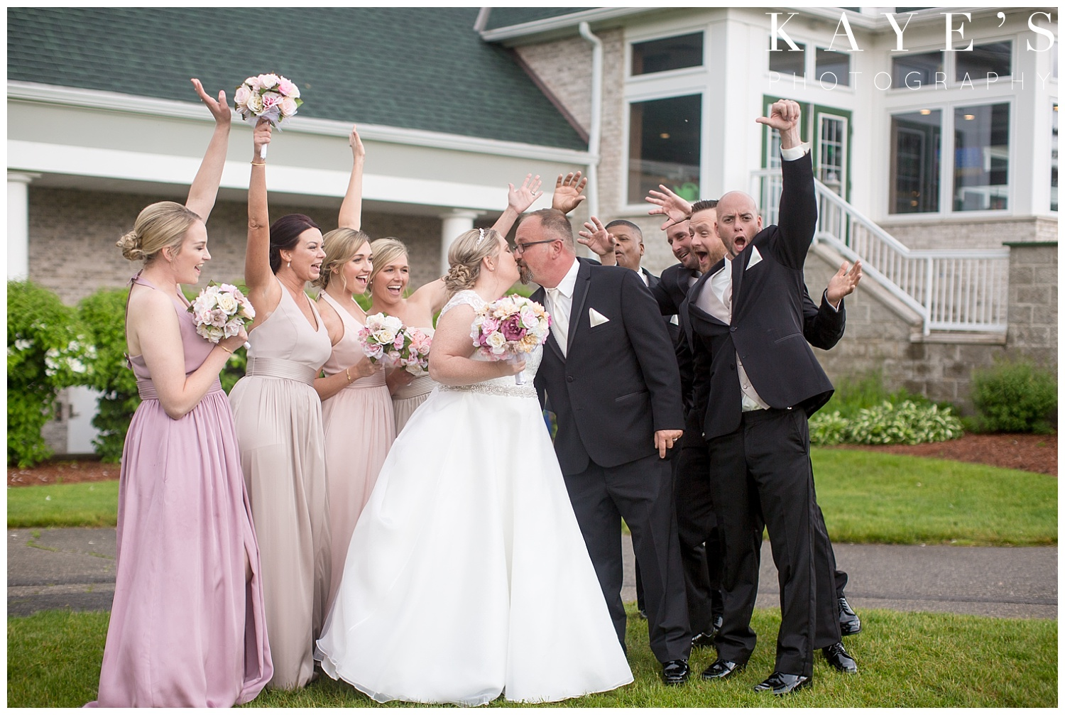 bridal party photos with bride and groom kissing