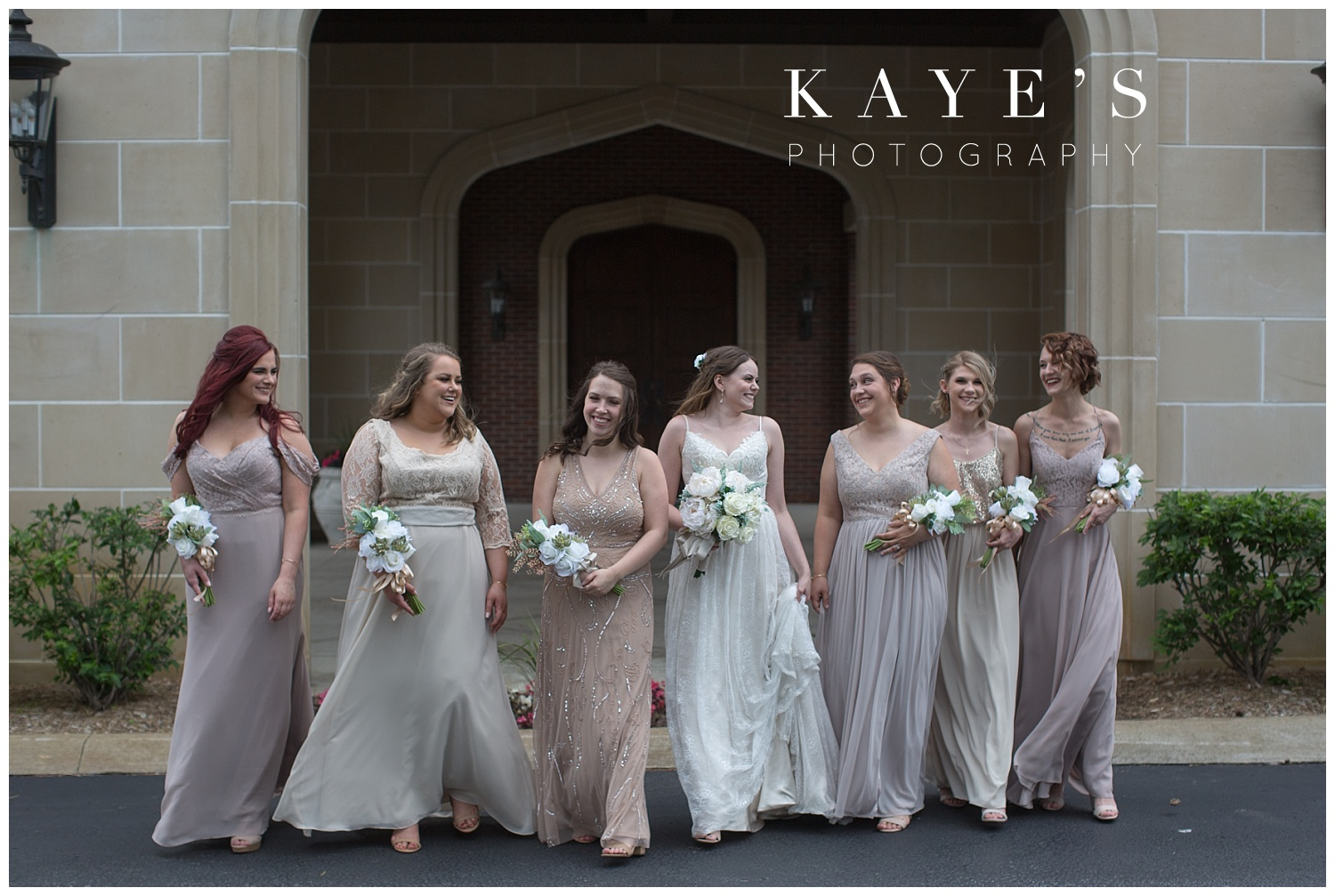 bride with bridesmaids walking in front of warwick hills in grand blanc michigan