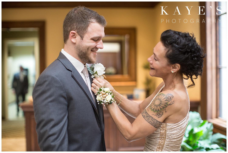 mother of groom putting flower on groom before wedding ceremony