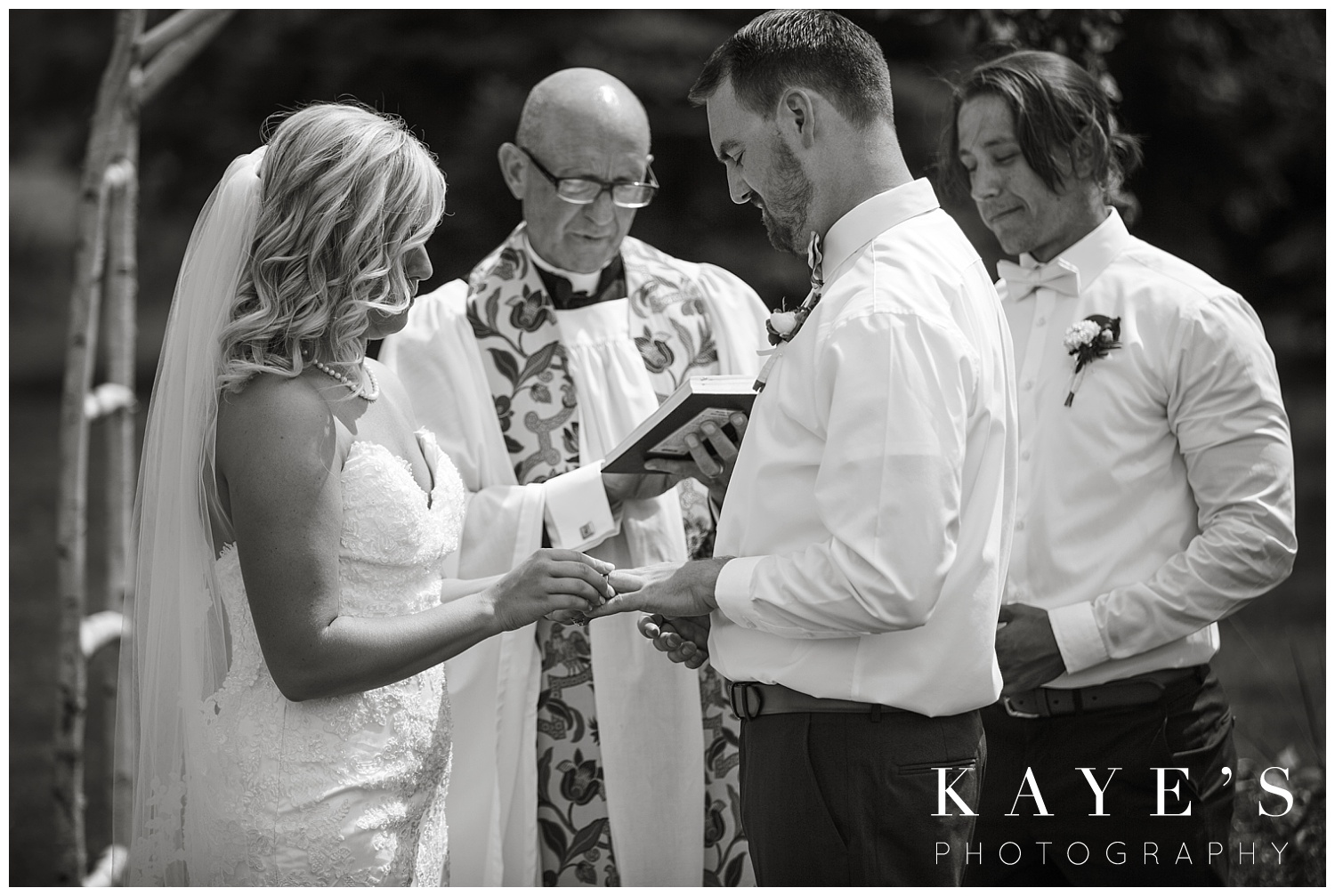 bride putting grooms wedding ring on during wedding ceremony in davison michigan