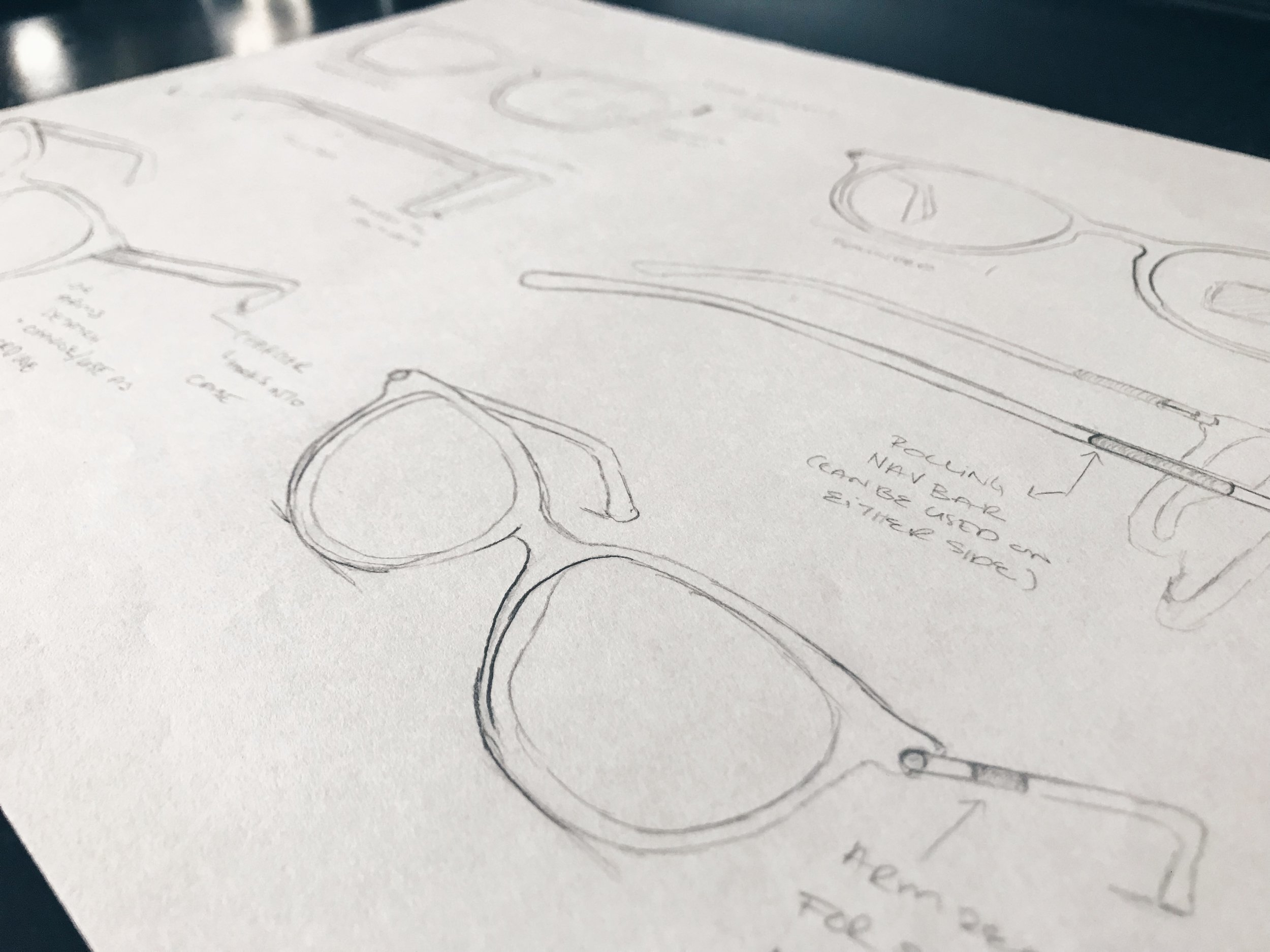 Initial product design sketches - While designing the user interface, I hit a wall. How would people be interacting with this device? I began to go through iterations of product designs. I needed to determine how users would interact with the interface. I went through, talk-activation, a touchpad through the arm of the glasses, and even eye tracking technology, but settled on something a little different. I decided to develop a ring for navigation. This capacitive sensor ring enables discreet easy access use, that doesn't require the users to lift a hand.