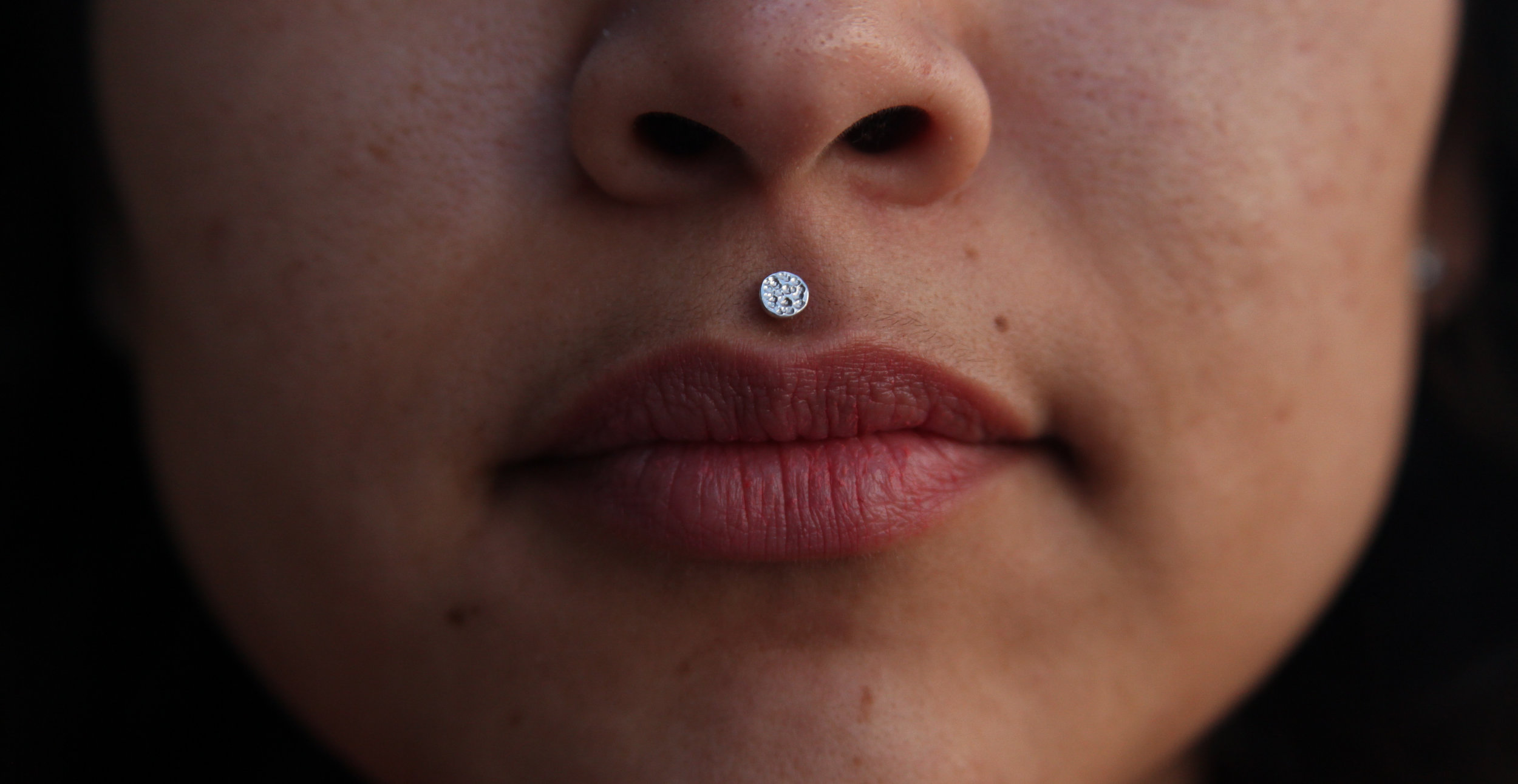 Lip Piercing - Lip piercings have a variety of placements around the lip tissue. This includes directly above the Cupid's Bow (the philtrum, pictured left), traditional labret piercings, placed in the center under the lower lip, and any sort or paired placement (colloquially referred to as snakebites, spiderbites, etc.). These piercings see a significant amount of swelling and need a longer piece of jewelry at the beginning, but also need downsizing relatively early on in the healing process.