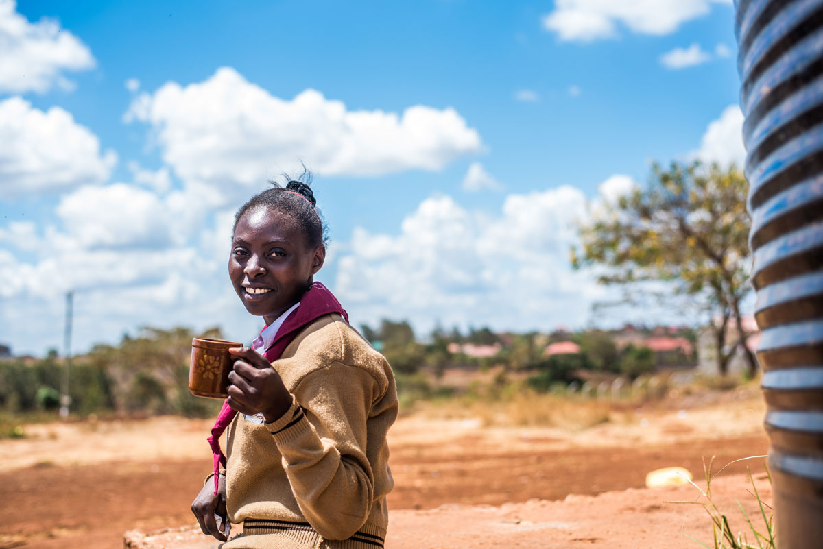 Impact-Water-Kenya-happy-female-student-with-water.jpg