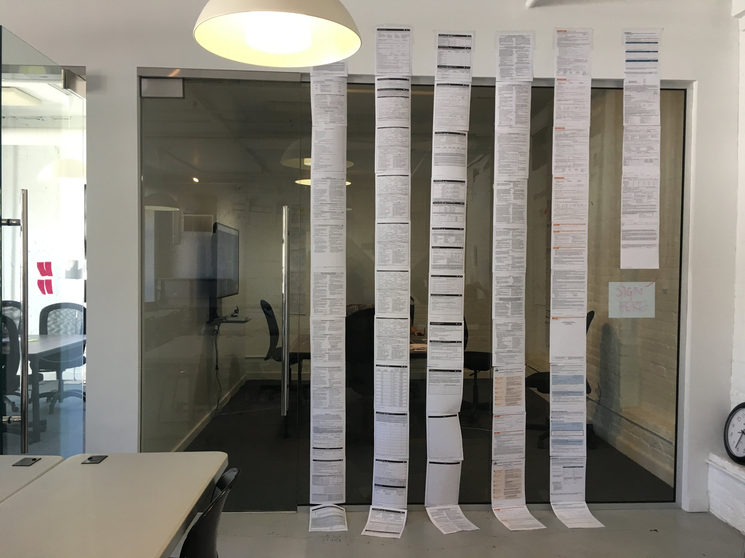 Setting up our war room. We wanted to remember the weight of the original application, so we printed it out and taped it together.