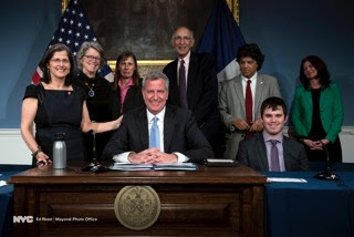 A HISTORIC MOMENT: Mayor de Blasio was joined at the bill-signing ceremony at City Hall by, from left: Council Member Helen Rosenthal, HLAA-NYC Chapter President Katherine Bouton, MOPD Deputy Commissioner Kleo King, Chapter member and accessibility advocate Jerry Bergman, MOPD Deputy Commissioner Robert Piccolo, former City Council student intern Edward Friedman, and Council Member Elizabeth Crowley.