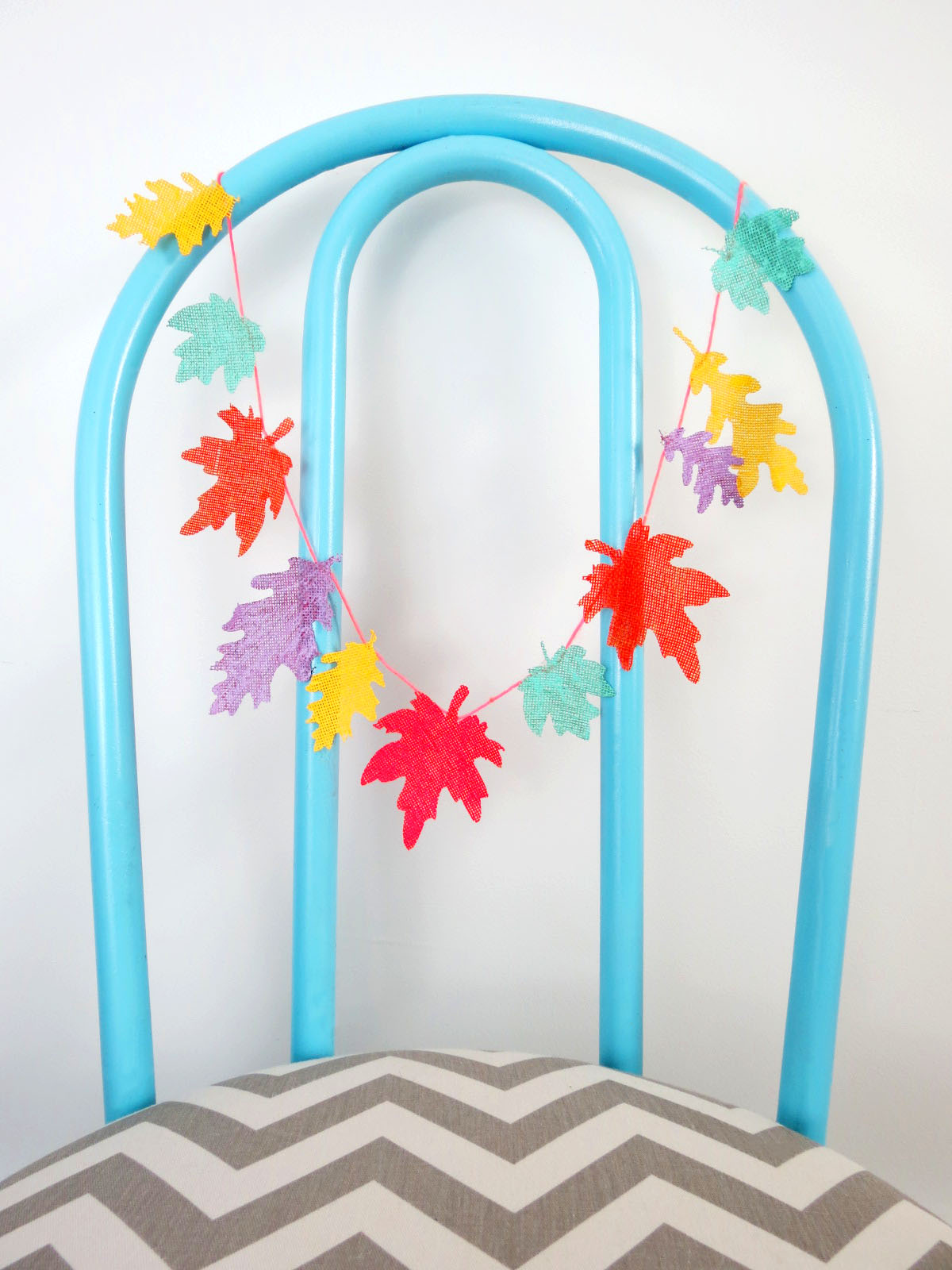 Dress up your Thanksgiving tablescape with this DIY Colorful Leaf Garland! These painted leaves will add a burst of color and are perfect for the kids' table! #thanksgiving #kidstable #colorfulthanksgiving