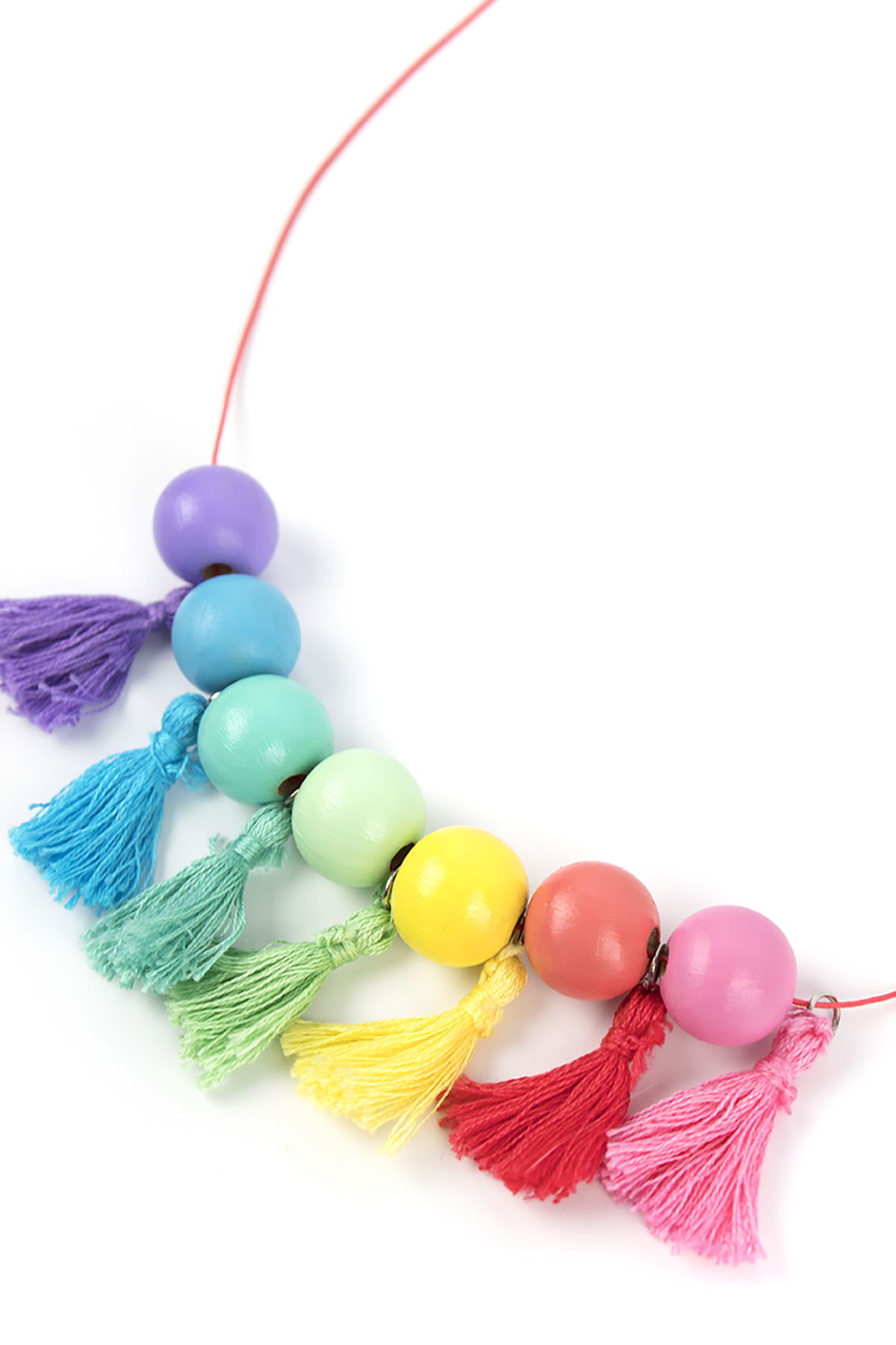 Add a little color to your wardrobe with this DIY Wood Bead Tassel Necklace. It features painted beads, DIY tassels, and a customizable palette. Make one for your closet today! #diyjewelry #rainbow #stpatricksday