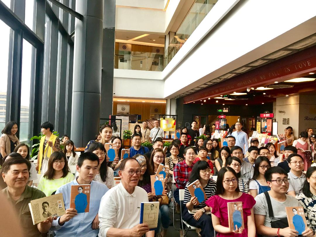 Audience members hold up their copies of  Chasing the Modern  along with Tony Hsu at Sisyphe Bookstore in Hangzhou, China.