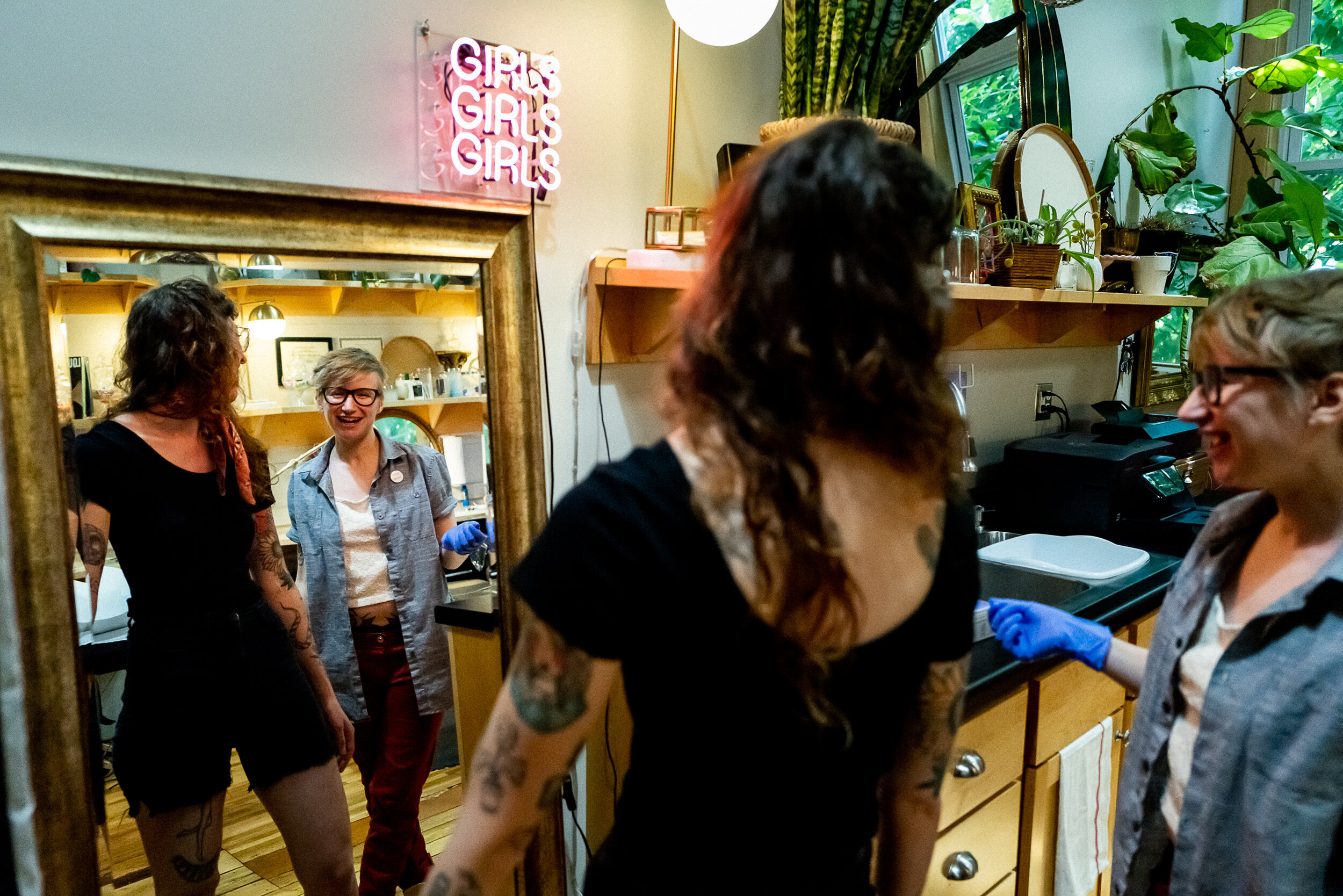 """""""When I released myself from being defined as a woman, all of a sudden I could feel very pretty. I could look in the mirror and say 'I'm neither of you and I'm both of you'."""" Ray consults with a client in their tattoo studio, The Aldrich, where the motto is """"Respect Every Body""""."""