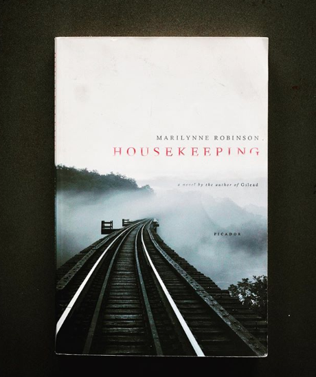 """Housekeeping  by Marilynne Robinson.  Invite curiosity for the dark, investigations of the underworld, for what's been sealed over, frozen shut. Otherwise, this moonless lake might orphan us from tributaries of loss and abandonment that need our attention most. But we're often told to keep scrubbing. Keep brushing that hair, that toilet. Wear twice-ironed button-ups and bleach everything. Purell your life clean. Upkeep, housekeep, keep the veneer of civility polished while scars and skeletons roil beneath to encrust the unaddressed with overcivilized worship of the prim and proper. Such posturing sweeps """"waste"""" into unseen corners and under bridges, thumbing corks into bottles to trap the ferment. This slow violence of concealment scrapes the psyche like glacial creep, ice-floods inching us ever closer to reset. Tend not to the dark night of the soul and we remain in dollhouses of perpetual adolescence. Instead this: pull up the anchor, pop the cork, and drift our vessels into waters below the fast-moving train tracks of modern life, into ink-fog night, fingerbones paddling into more honest directions, even when, in the distance, our house rips apart in fantastic blaze, set by us, crude purchase from the night but an offering, too, signal fires suggesting where we go, and what we do, next."""
