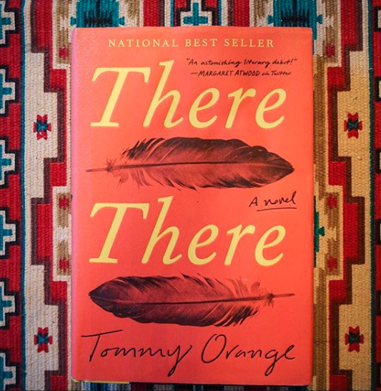 """There There, by Tommy Orange.  Shots fired, holes everywhere, draining and bleeding, wounds old and new, past and present, staring through your own reflection, everywhere. How does one move forward, stay visible, while also dancing and drumming into tradition, into heritage? Spiders carry webs, miles of filament, both home and trap, and all lives they braid together, all of it, all the joy and pain, victory and violation, they all converge at the powwow for celebration and ceremony and robbery, white guns and white violence manifest. There is no longer a """"there"""" to locate with any certainty, when home's been paved over, homogenized, settled, and surveilled by mall cops and modern palates. Colonialism fires its white-hot bullets, so hard, so breakneck. In this flurry, where's Home, where's Mother, where's firm ground after Earth and the cultures that most respect Her are being turned into spectacle and artifact? Earth is everywhere: Earth is bullet. Earth is urban. Earth is imperial coliseum holding native ceremony. Earth is drone. Earth is feather. Shots fired, holes everywhere. Do you stay or flee? Perhaps you dance through the onslaught of bullet-rain, old moves and new ones, transformed ones. You dance any way and anyways, for sustenance, for survival, for grieving, for healing, for homecoming."""