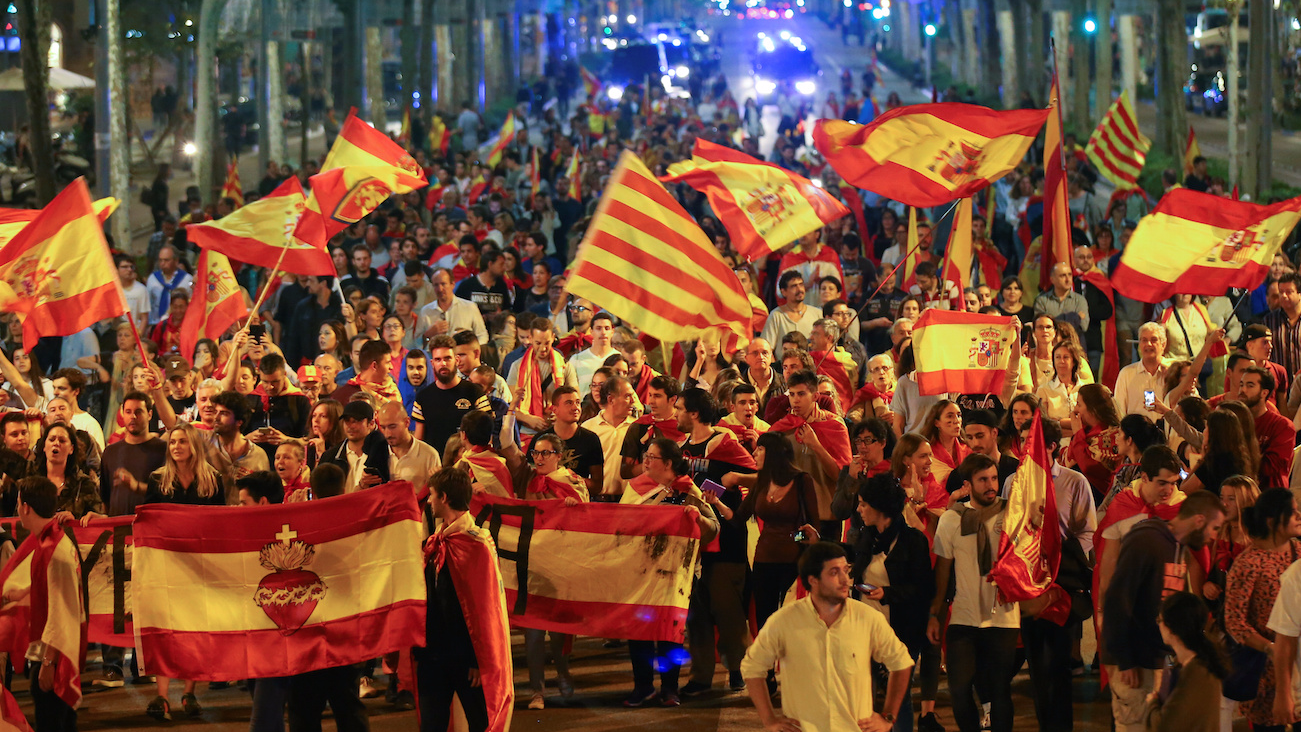 Pro-unity demonstrators wave Spanish and Catalan flags during a protest in Barcelona. REUTERS/Albert Gea