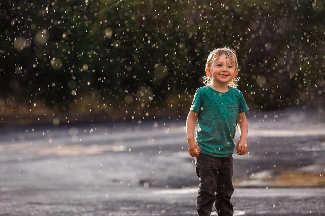 A beautiful summer rain started falling during sunset, and I had mere seconds to race in to the house, get my camera (which is almost always on my desk in the living room with lens attached) and capture this. It is one of my favorite images ever taken of my son.