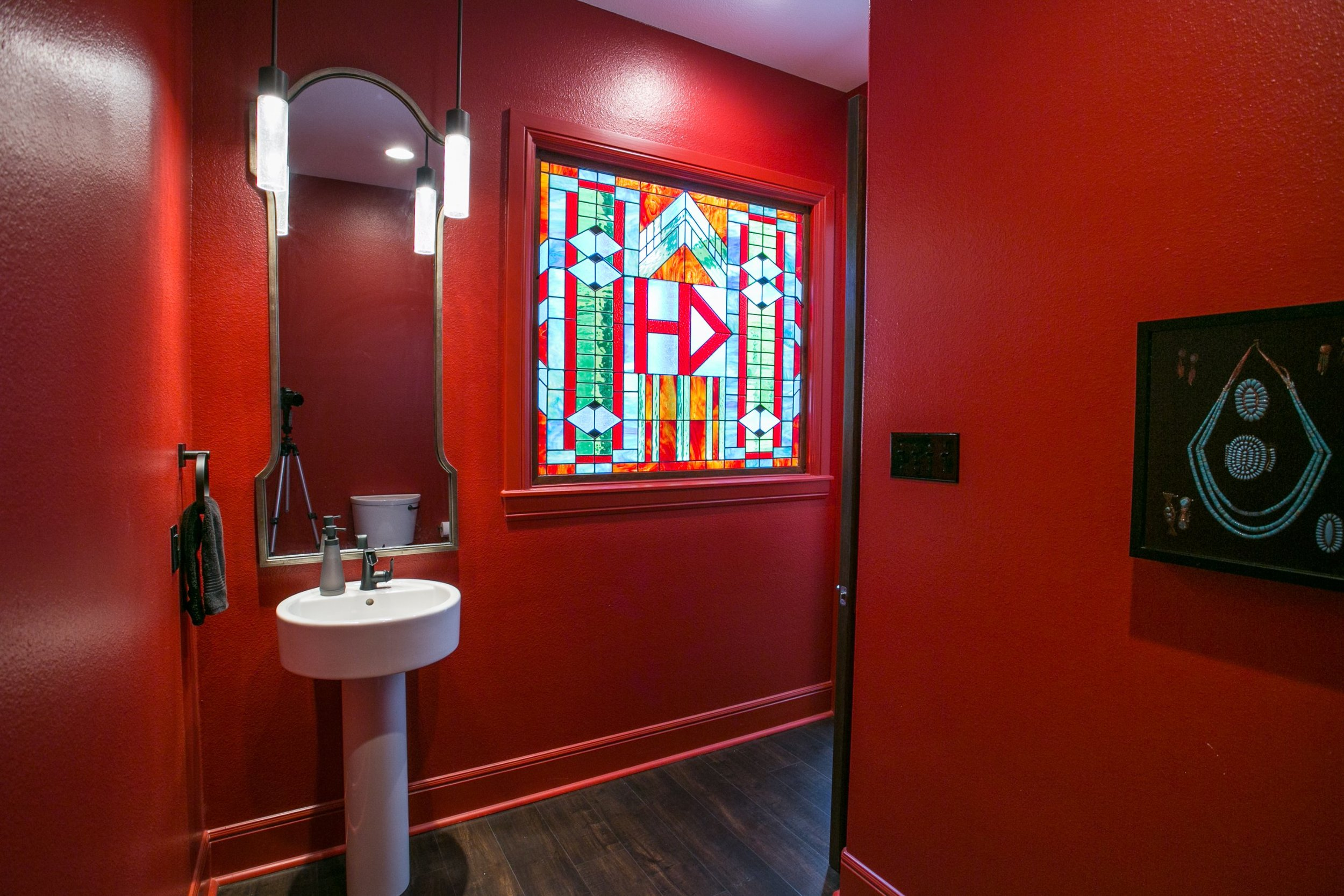 This custom stained-glass window, a gift to the husband, became the catalyst and focal point of the powder room and was given a prominent location in the plan in proximity of the front door. Also vintage turqoise jewelry framed in a black shadow box stands out on the red wall.