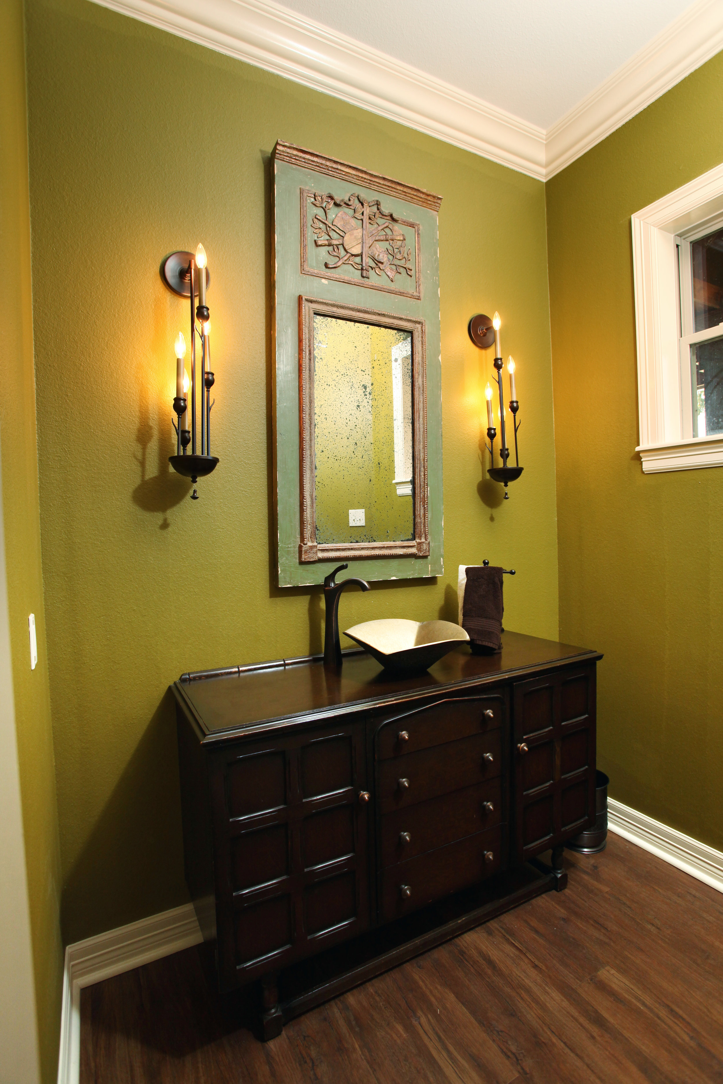 Unique sconces flanking an antique trumeau mirror over a repurposed chest of drawers in my clients ranch-house powder room make for a one-of-a-kind impression.